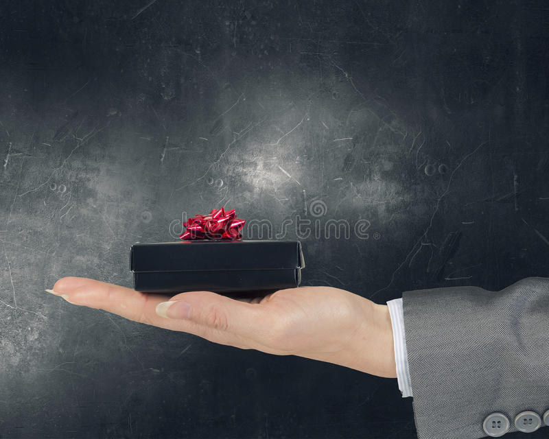 Woman presenting gift box . Mixed media. Close view of businesswoman hand holding gift box stock photo