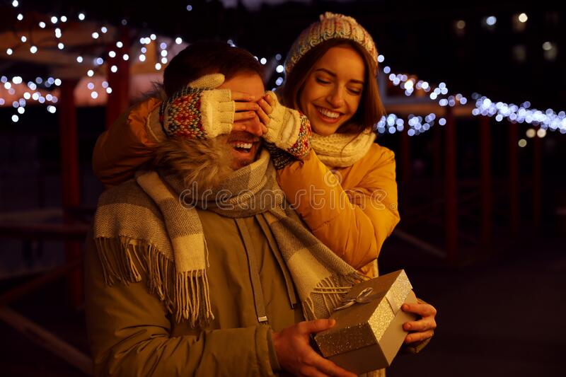 Woman presenting gift to boyfriend at Christmas fair. Happy couple royalty free stock photos