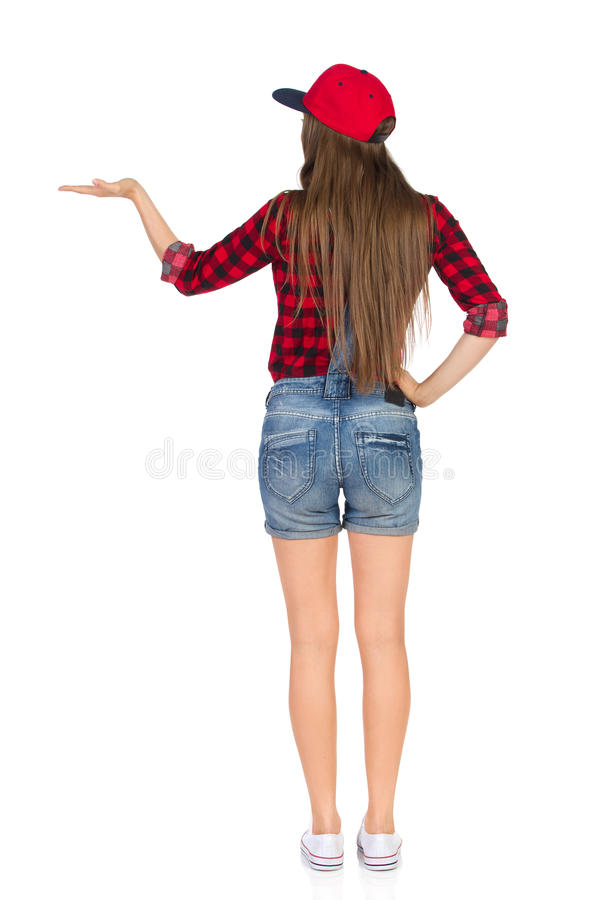 Woman Presenting Rear View. Woman in red lumberjack shirt, jeans dungarees shorts, white sneakers and red cap standing with hand raised, presenting something and royalty free stock image