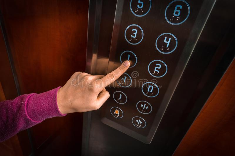 Woman pressing the button in the elevator interior royalty free stock image