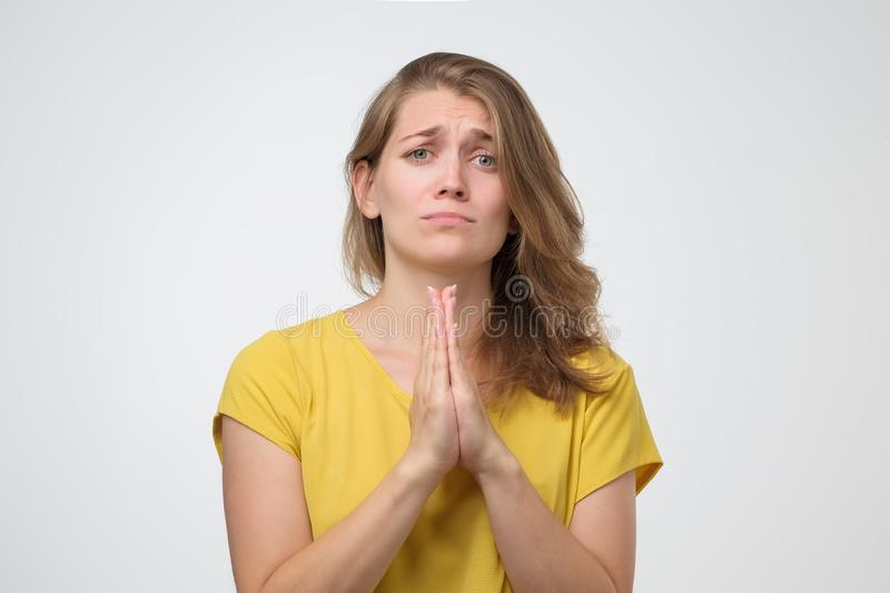 Woman pressing palms together begging pray for help stock images