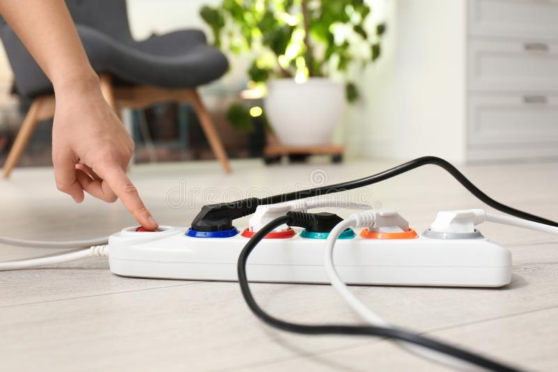 Woman pressing power button of extension cord on floor indoors. Electrician`s professional equipment. Woman pressing power button of extension cord on floor royalty free stock photos
