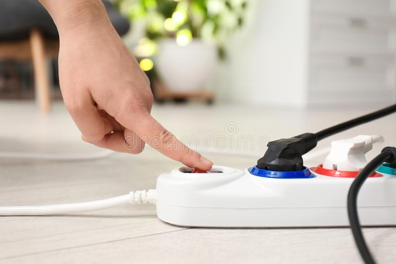 Woman pressing power button of extension cord on floor indoors. Electrician`s professional equipment royalty free stock image