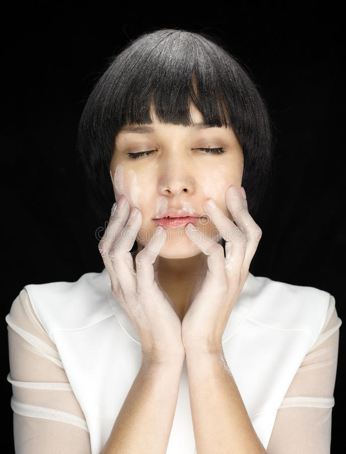 Woman with prints of flour on face. Close up of woman with closed eyes and white prints of flour on face on black background, hands on face stock photo