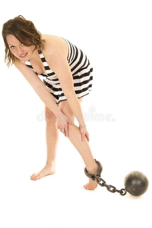 Woman in prison outfit skirt with ball and chain on foot royalty free stock photos