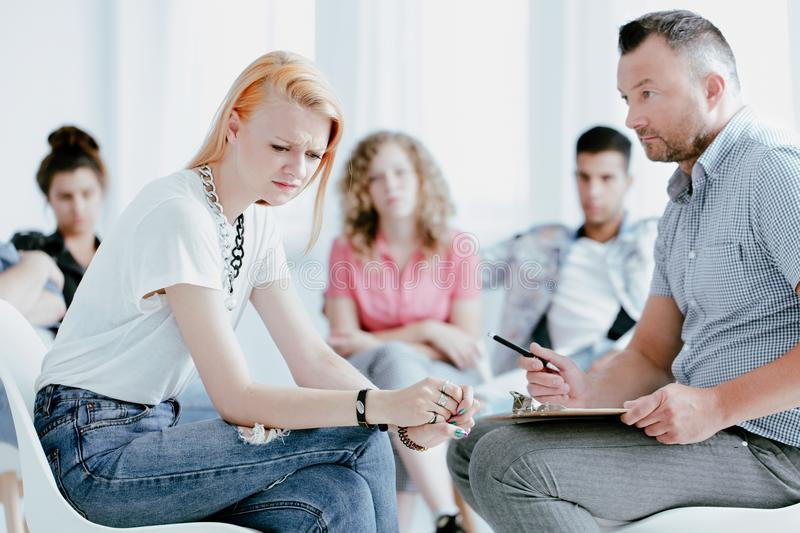 Woman with problem and psychologist. Young women with a problem sitting in front of a psychologist and talking about teenagers life royalty free stock photography