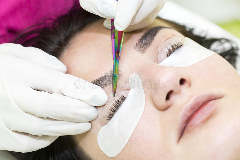 Woman on the procedure for eyelash extensions royalty free stock photography