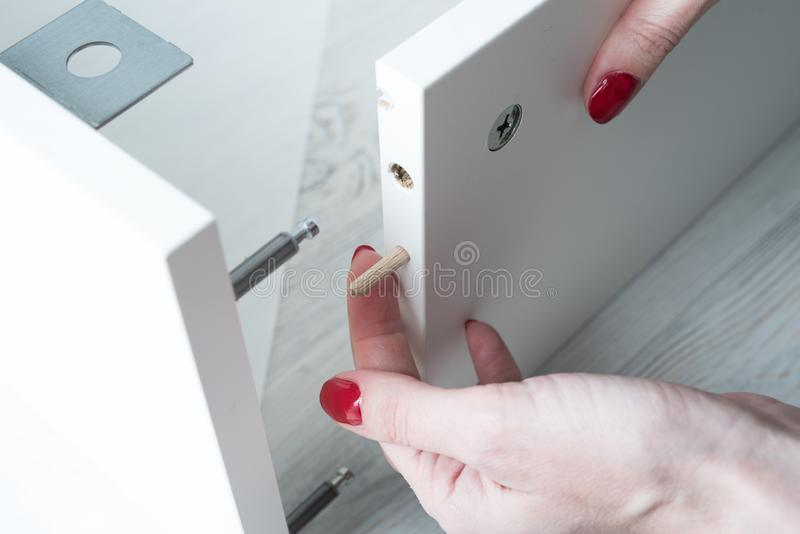 A woman inserts wooden pins into the sidewall of the furniture w royalty free stock photo