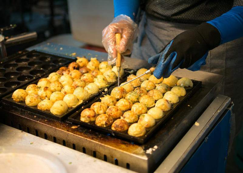 Woman process to cooking takoyaki at night maket. it most popular delicious snack of japan. stock photos