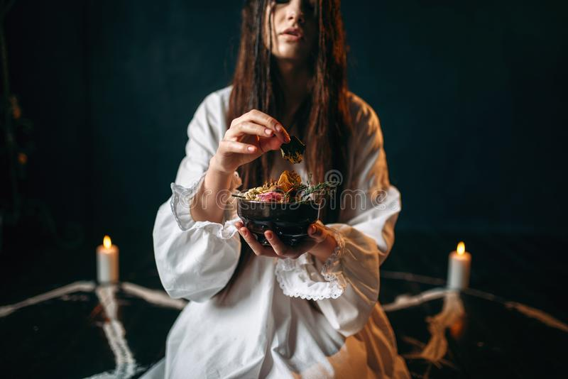 Woman produces a ritual of black magic, occultism. Young woman in white shirt sitting in the center of pentagram circle with candles and produces a ritual of royalty free stock images