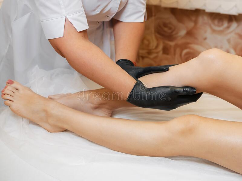 Woman professional beautician and masseur takes care of the feet of the girl client royalty free stock image
