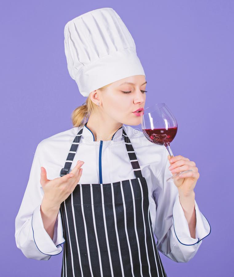 Woman professional chef hold glass of wine. Restaurant concept. Wine degustation. Which wine to serve with dinner. How. To pair wine and food like expert. Girl royalty free stock image