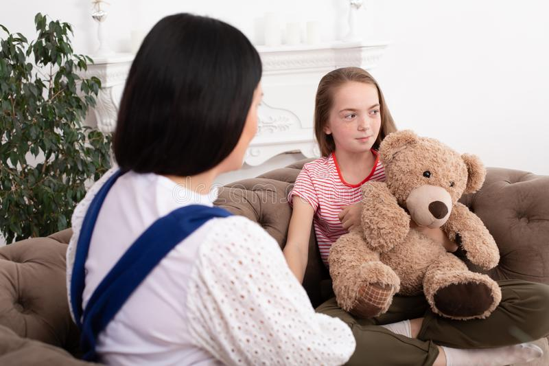 A woman is a professional child psychologist talking with a teenage girl in her cozy office. Psychological assistance to children royalty free stock image