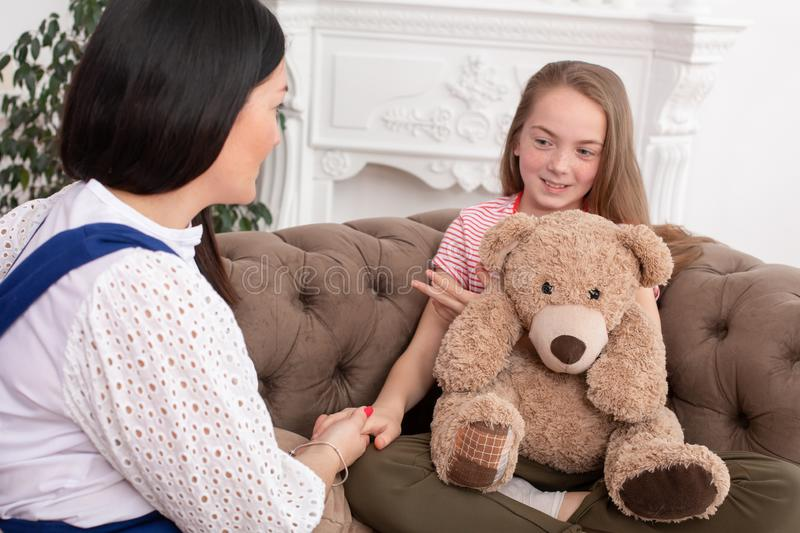 A woman is a professional child psychologist talking with a teenage girl in her cozy office. Psychological assistance to children stock photography