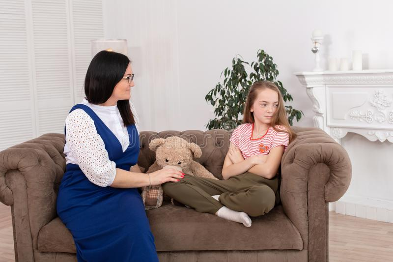 A woman is a professional child psychologist talking with a teenage girl in her cozy office. Psychological assistance to children royalty free stock photography