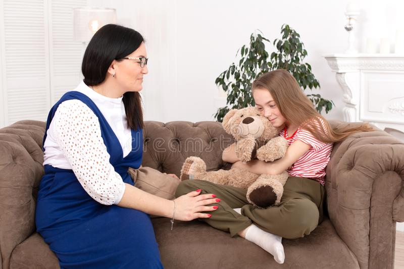 A woman is a professional child psychologist talking with a teenage girl in her cozy office. Psychological assistance to children stock photo