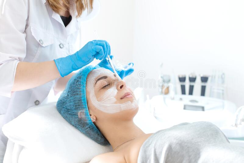Woman professional doctor beautician applies a mask on a patient`s face for skin care. Cosmetic procedures for skin rejuvenation royalty free stock photos