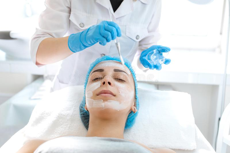 Woman professional doctor beautician applies a mask on a patient`s face for skin care. Cosmetic procedures for skin rejuvenation royalty free stock photography