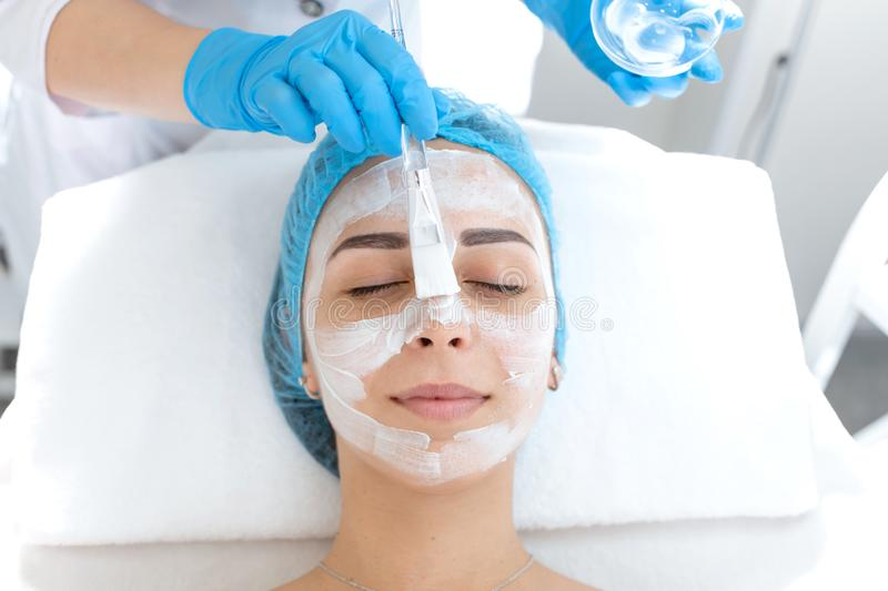 Woman professional doctor beautician applies a mask on a patient`s face for skin care. Cosmetic procedures for skin rejuvenation stock photography