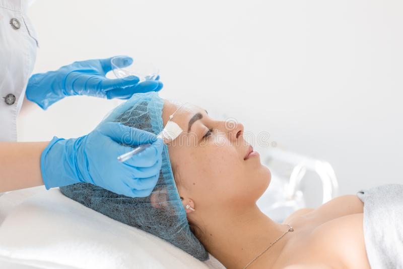 Woman professional doctor beautician applies a mask on a patient`s face for skin care. Cosmetic procedures for skin rejuvenation royalty free stock images