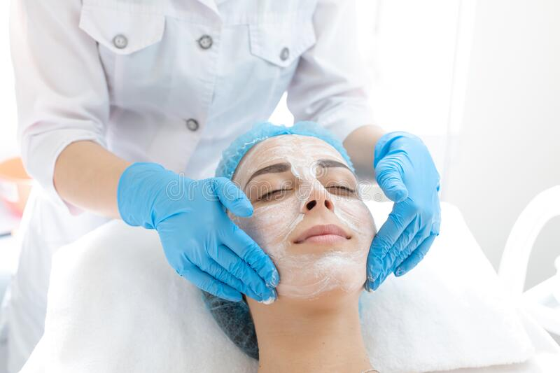 Woman professional doctor beautician applies a mask on a patient`s face for skin care. Cosmetic procedures for skin rejuvenation royalty free stock photo