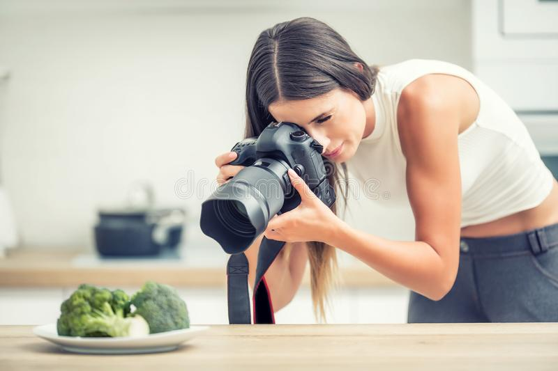 Woman professional photographing plate with broccoli. Food photographer working in kitchen studio royalty free stock photos