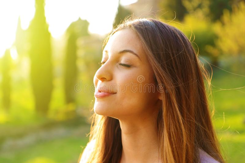 Woman profile portrait breathing deep fresh air with nature in background.  royalty free stock images