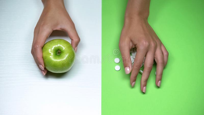 Woman proposing apple instead pills, healthy way of life, vitamins, macro shot. Stock photo royalty free stock images