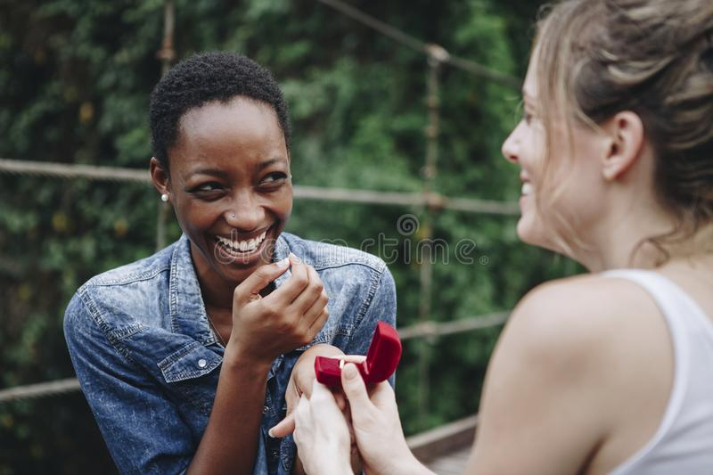 Woman proposing to her happy girlfriend outdoors royalty free stock photos