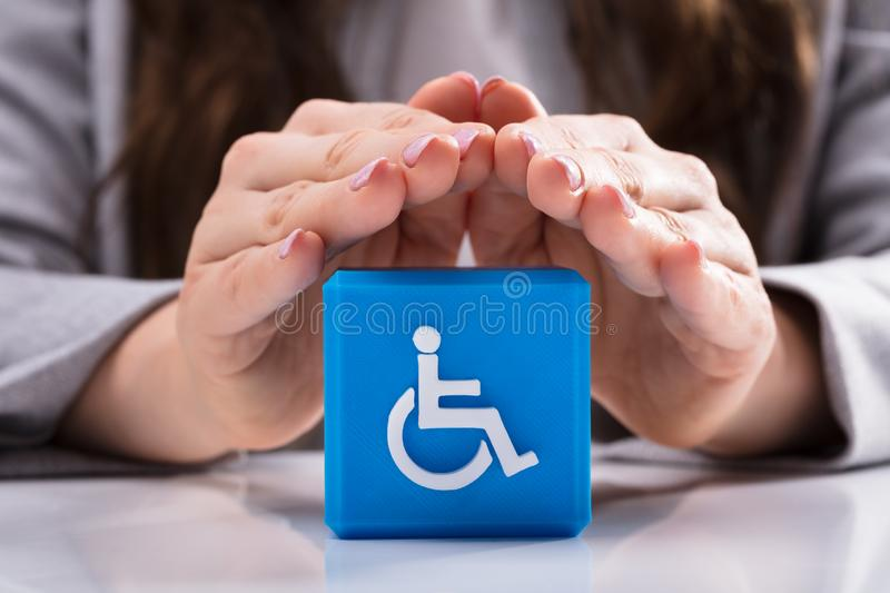 Woman Protecting Cubic Block With Disabled Handicap Icon royalty free stock images