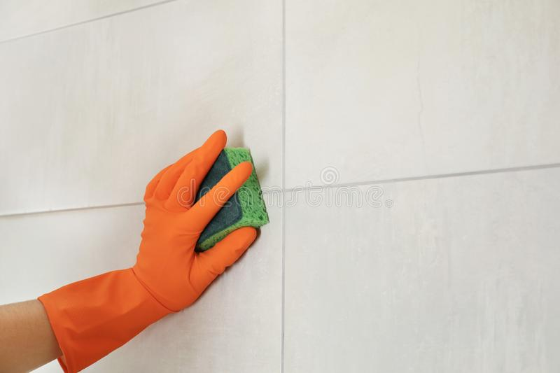 Woman in protective glove cleaning bathroom wall with sponge stock photography