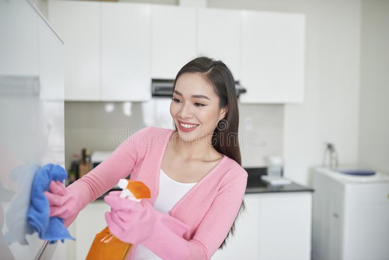 Woman in protective gloves cleaning refrigerator with rag indoor stock image
