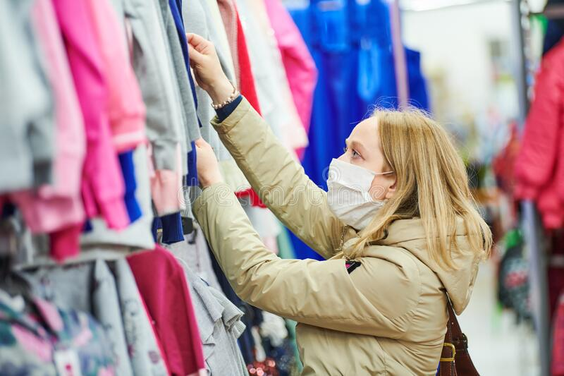 Woman in protective mask shopping clothing in apparel shop at coronavirus epidemic royalty free stock image