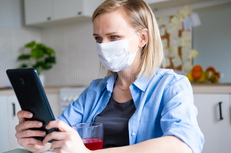 Woman in protective medical mask using digital tablet for video call talking friends and parents, girl sitting at home. Kitchen fun greeting online by computer royalty free stock photo