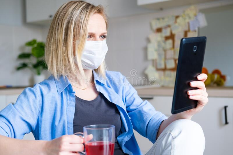 Woman in protective medical mask using digital tablet for video call talking friends and parents, girl sitting at home. Kitchen fun greeting online by computer stock photo