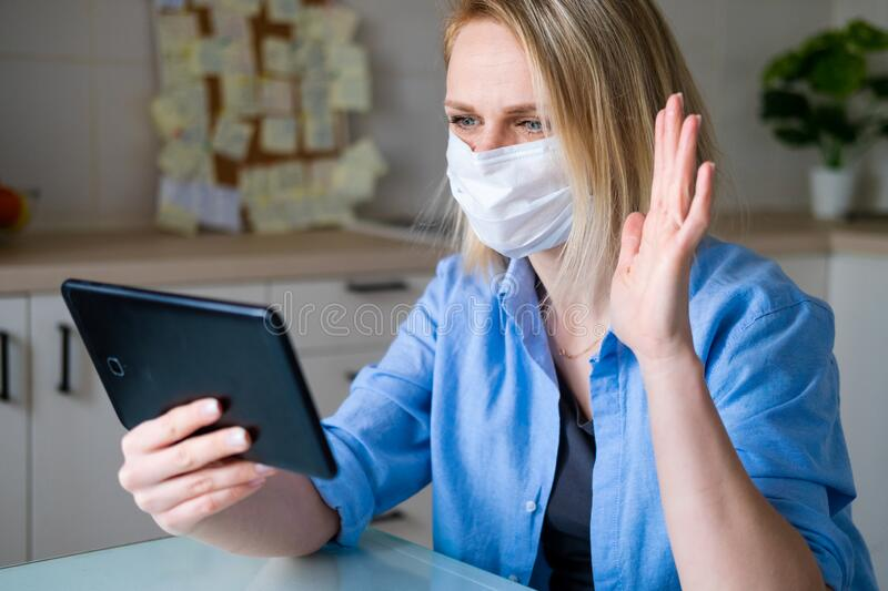 Woman in protective medical mask using digital tablet for video call talking friends and parents, girl sitting at home. Kitchen fun greeting online by computer royalty free stock images
