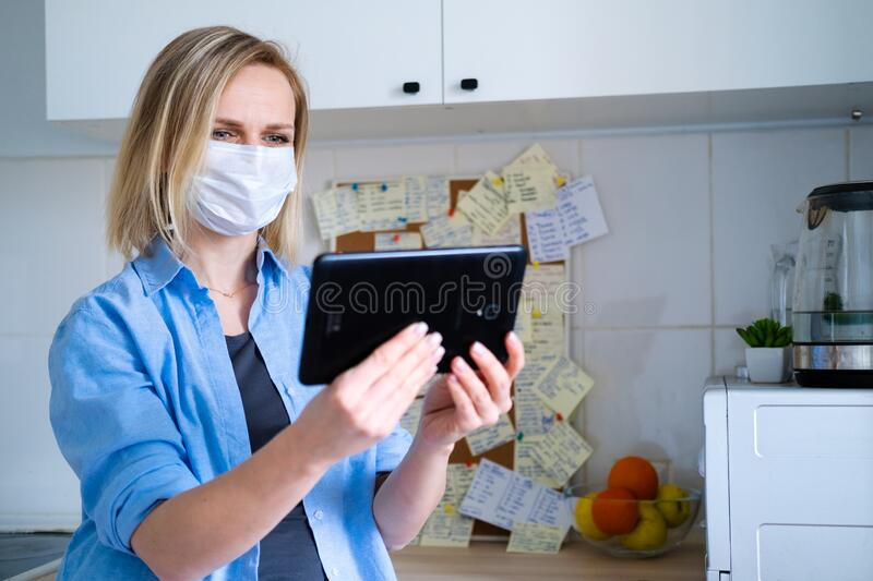 Woman in protective medical mask using digital tablet for video call talking friends and parents, girl sitting at home. Kitchen fun greeting online by computer royalty free stock image