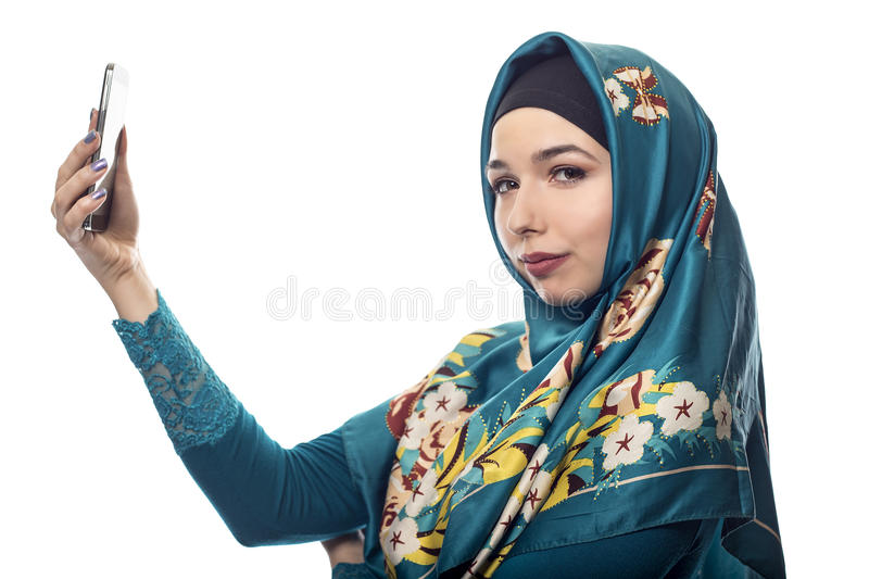 Woman Proudly Showing off Hijab via Selfie. Middle Eastern or East European female proudly showing her conservative fashion via social networking by taking a royalty free stock photos