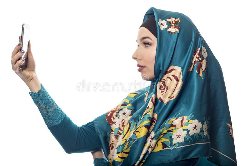 Woman Proudly Showing off Hijab via Selfie. Middle Eastern or East European female proudly showing her conservative fashion via social networking by taking a royalty free stock image
