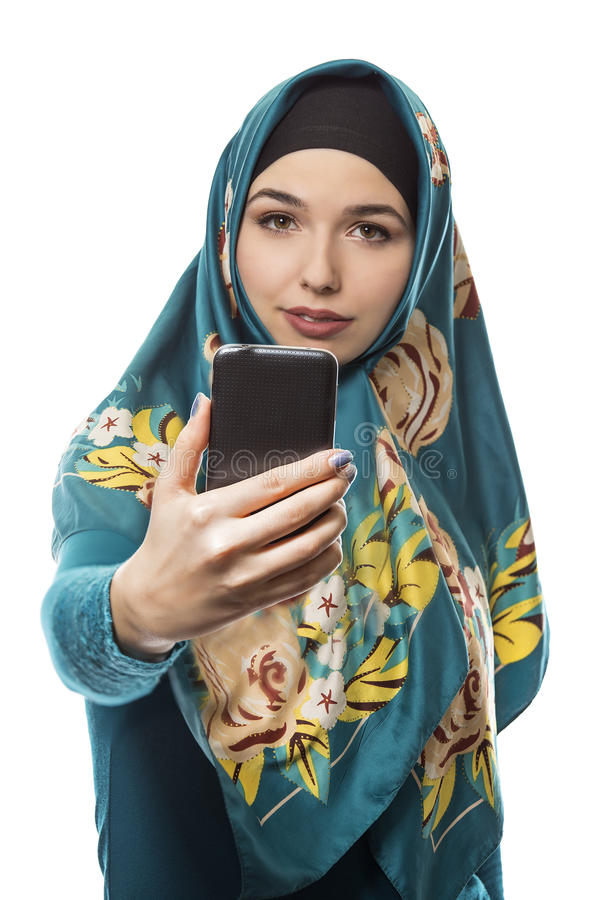 Woman Proudly Showing off Hijab via Selfie. Middle Eastern or East European female proudly showing her conservative fashion via social networking by taking a stock photo