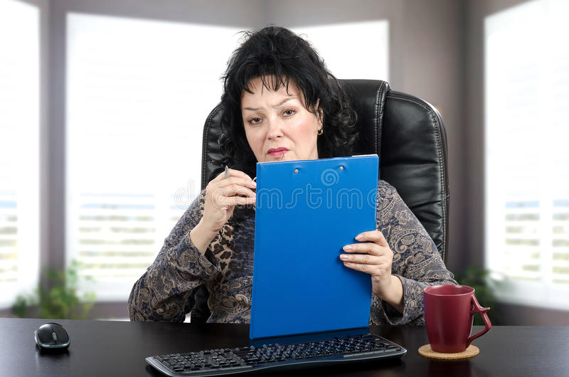 Woman psychiatrist looking at camera. Mature woman sits in black leather office chair and sympathetically looks at the camera. She is certified psychiatrist stock image
