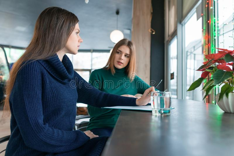 Woman psychologist counseling talking to a young girl, psychotherapist gives psychological help in cafe coffee shop royalty free stock images