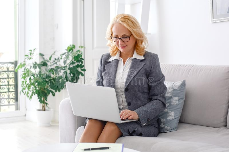 Woman psychologist portrait sitting at casual home office working on laptop. Middle-aged woman psychologist sitting at casual home office wearing eyeglasses royalty free stock photography