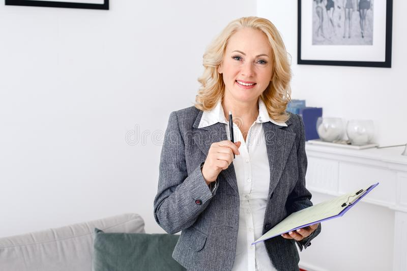 Woman psychologist portrait standing at casual home office holding paper holder royalty free stock photo