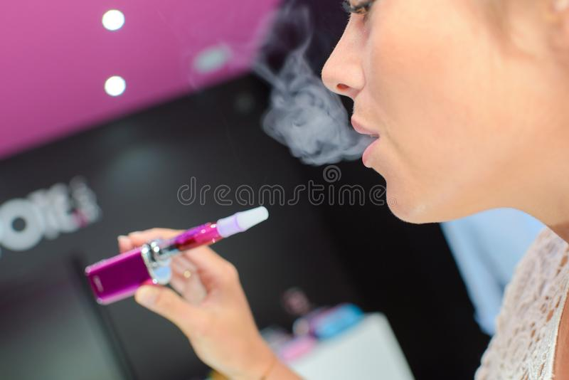 Woman puffing an e-cigarette. Woman stock photo