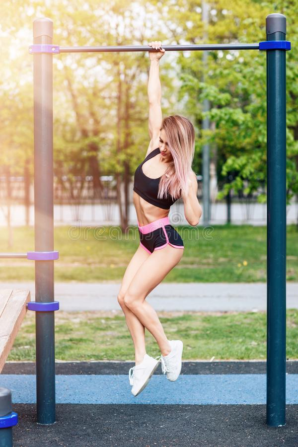 Woman pull-ups herself up on bar on sports ground in park. royalty free stock image