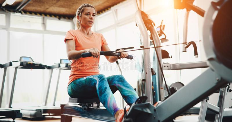 Woman pulling on row machine in fitness stock images