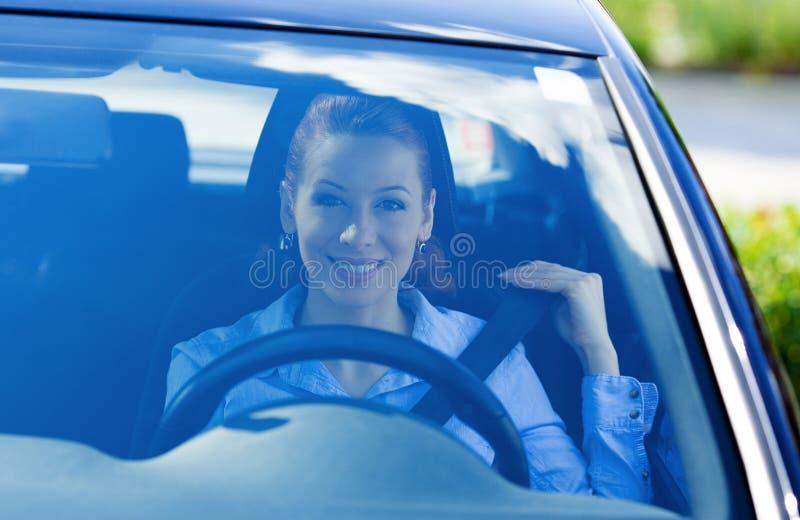 Woman pulling on seatbelt inside black car stock image