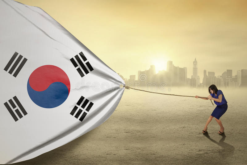 Woman pulling a south korean flag. Portrait of young businesswoman pulling a south korean flag, shot outdoors stock image