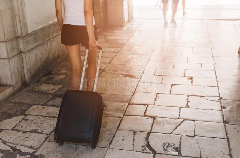 Woman pulling wheeled suitcase bag. And walking through old city stock images